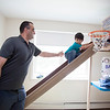 Baraa Alloh (right), 3, climbs up a bed built for him by Nashoba Valley Technical High School students while his father, Mohammed, watches in their Concord home. Lowell Sun/Chris Lisinski