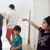 Cidra Alloh (right), 5, and Baraa Alloh, 3, watch as students from Nashoba Valley Technical High School work with their teacher to construct a bed for the Alloh family, who came to the United States as Syrian refugees. Lowell Sun/Chris Lisinski
