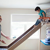 Mohammed Alloh (left) waits for his son, Baraa, 3, to use a new slide attached to a bed built by Nashoba Valley Technical High School students. Lowell Sun/Chris Lisinski