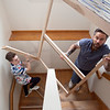 Luke Boucher (left), a student at Nashoba Valley Technical High School, and Jonathan Pryor, the school's carpentry instructor, carry a piece of a bed students constructed up the stairs at the home of a Syrian refugee family in Concord on Thursday. Lowell Sun/Chris Lisinski