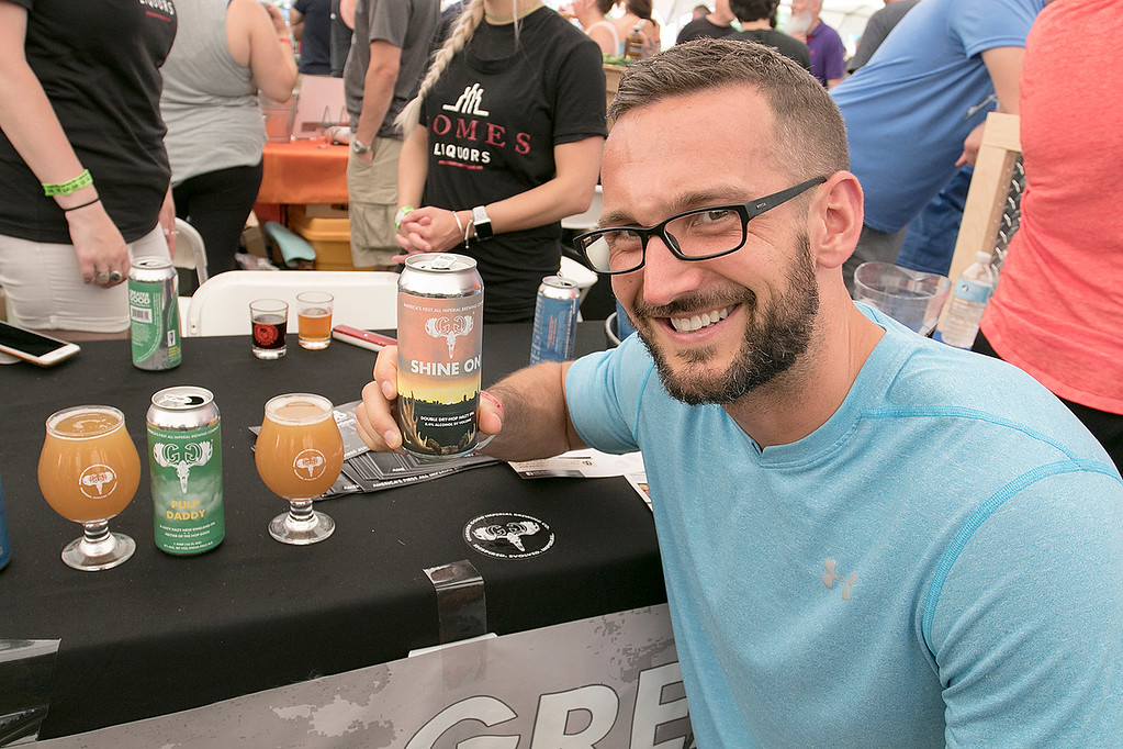 ". The 2019 Nashua River Brewers Festival held at Riverfront Park in Fitchburg Saturday, June 29, 2019. the festival was put on by ""Beers for Good\"" and the City of Fitchburg. Holding up a beer called \""Shine On\"" by Greater Good Imperial Brewing Company one of the many beer companies showing their beers at the festival is Justin Sparks of Fitchburg. SENTINEL & ENTERPRISE/JOHN LOVE"