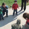 kids are looking at a caterpillar
