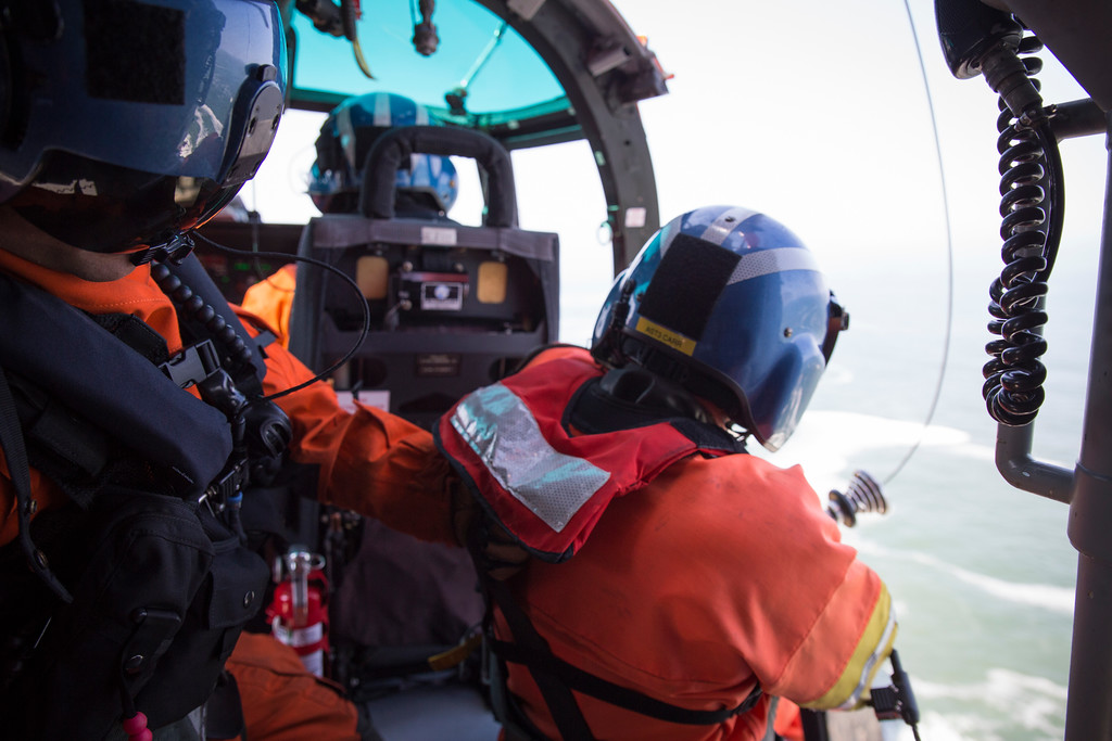 . Flight mechanic Brent Alexander checks and speaks with rescue swimmer Adam Carr before he takes off his radio communications and is lowered onto the steep terrain.  (Sam Armanino - Times-Standard)