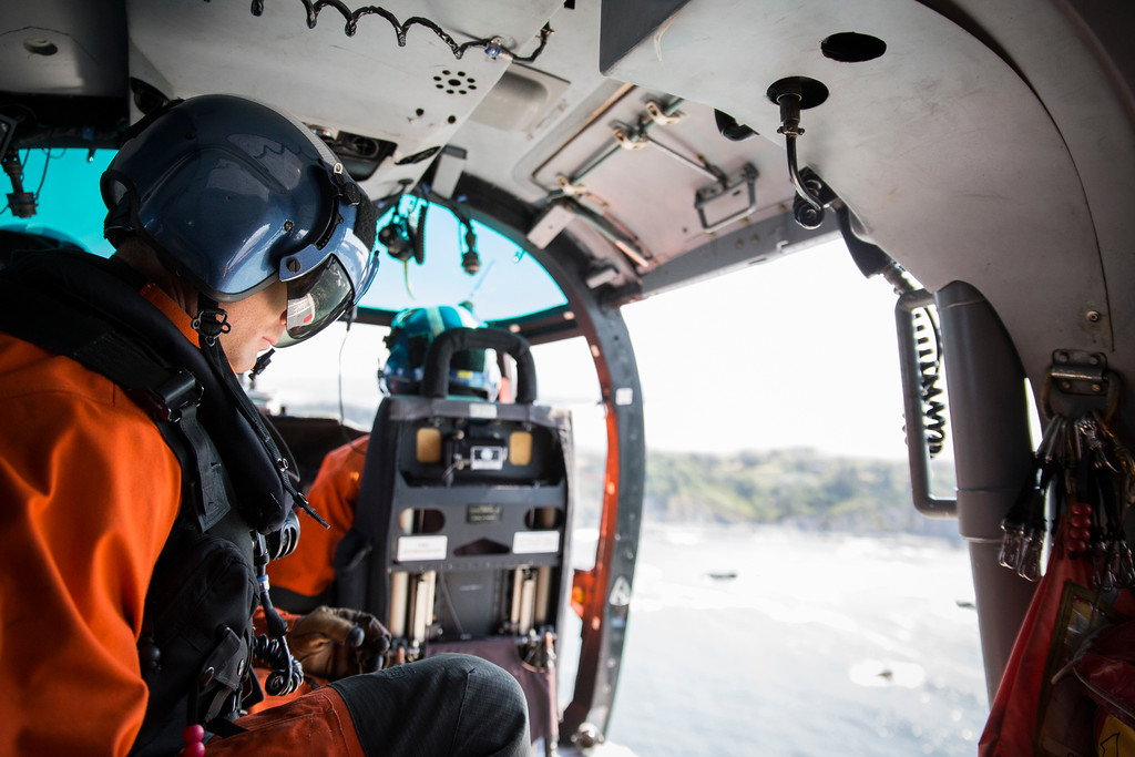 . Brent Alexander, flight mechanic, scans over the horizon as the flight crew hover just off the coast of Patrick\'s Point.  (Sam Armanino - times-Standard)