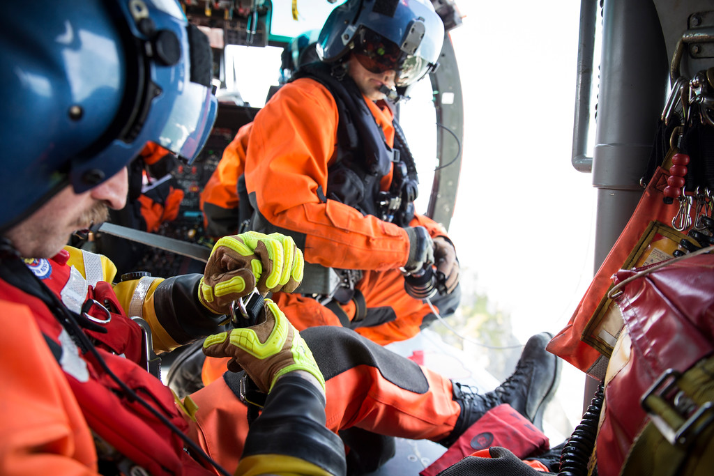 . Rescue swimmer Adam Carr clips himself to the cable as he prepares to be lowered in order to hoist a rescue dummy off the side of Wedding Rock on Aug. 2.  (Sam Armanino - Times-Standard)