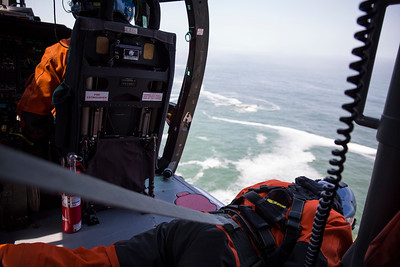 Flight mechanic Brent Alexander leans out of the helicopter to get a better look at his rescue swimmer Adam Carr as he relies on only hand signals to communicate.  (Sam Armanino - Times-Standard)