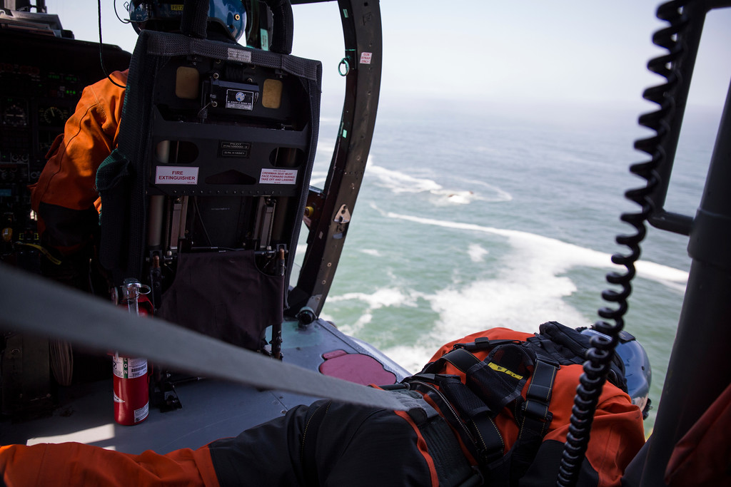 . Flight mechanic Brent Alexander leans out of the helicopter to get a better look at his rescue swimmer Adam Carr as he relies on only hand signals to communicate.  (Sam Armanino - Times-Standard)