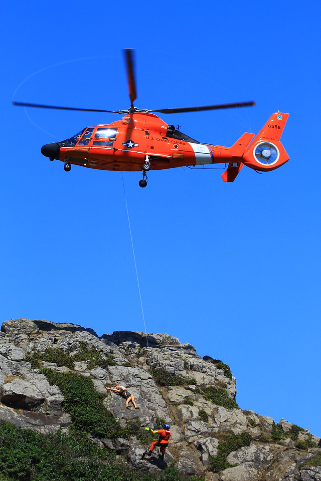 The pilots main goal is to hold the bright orange Dolphin helicopter as steady as possible while rescue swimmers are attached by cable.  (Sam Armanino - Times-Standard)
