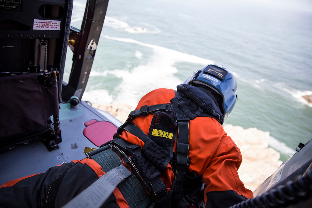 . Brent Alexander\'s job as flight mechanic is to be the eyes and ears on Adam Carr, rescue swimmer, as the pilots hold them steady above Wedding Rock.  (Sam Armanino - Times-Standard)