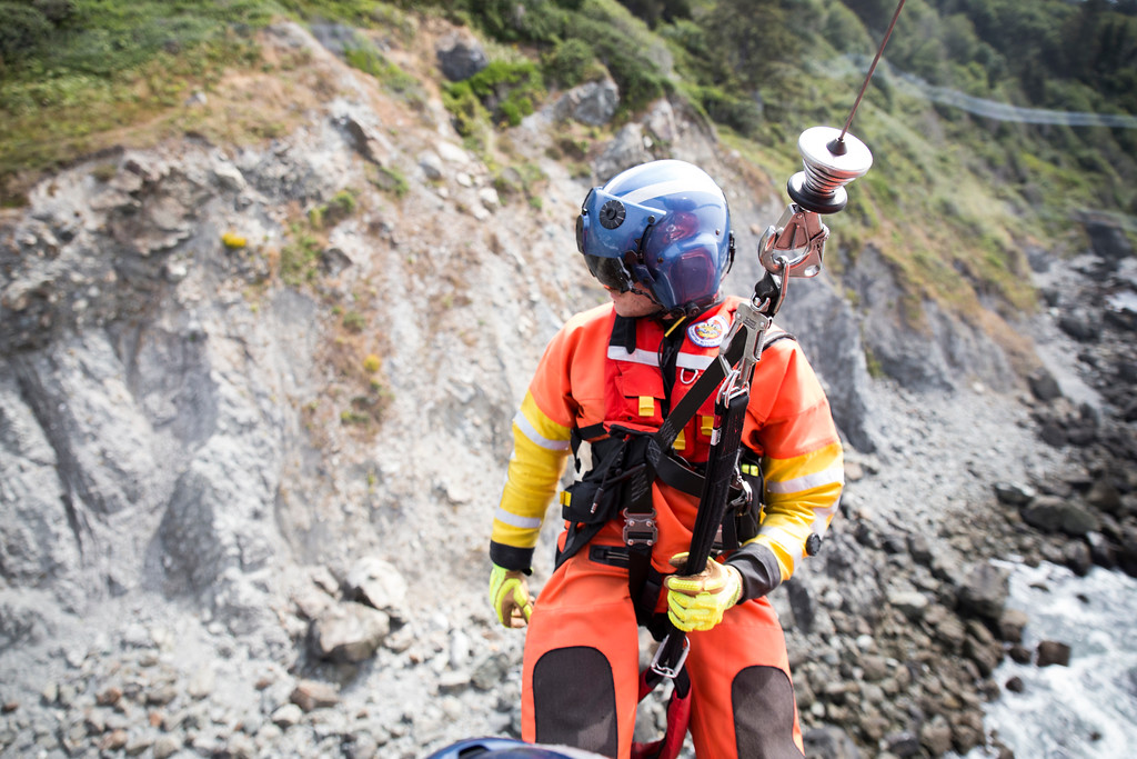 . Rescue swimmer Adam Carr begins to lower down. As a flight mechanic, Brent Alexander is in charge of lowering and lifting Carr for rescue hoists.  (Sam Armanino - Times-Standard)