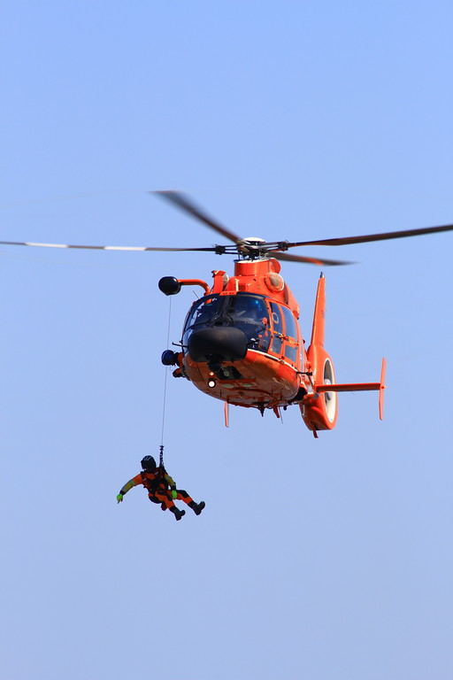 . One of the two flight rescue swimmers hangs out of the hovering helicopter in order to rescue a dummy positioned on a cliff side.  (Nick Bonner - Humboldt Bay Sector Coast Guard)
