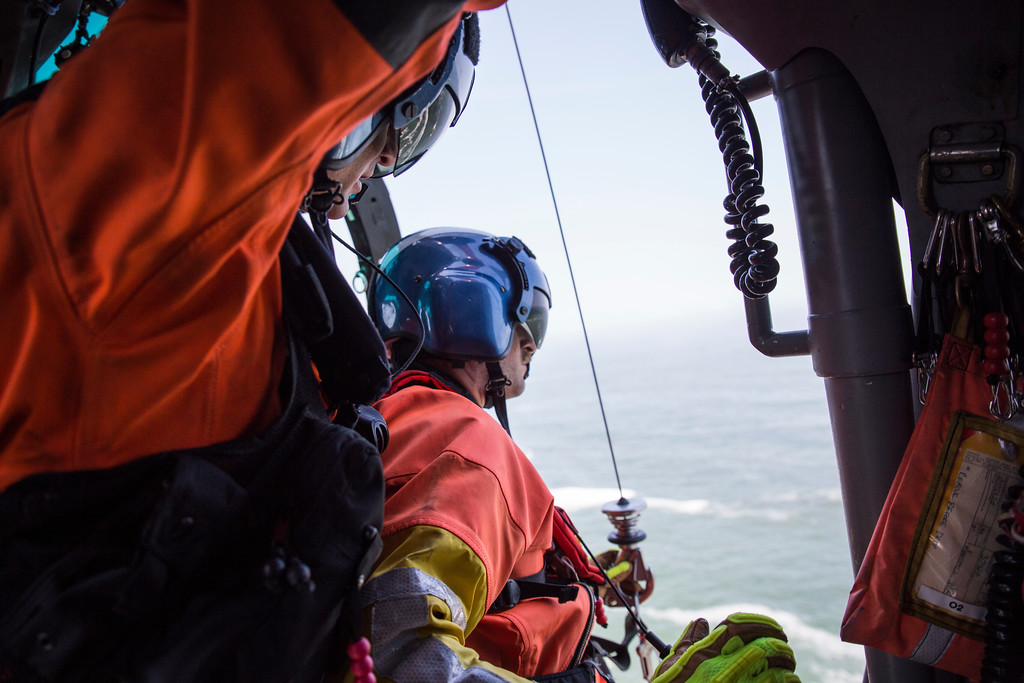 . Coast Guard crewmember Brent Alexander double checks the hoist equipment to lower rescue swimmer Adam Carr during a cliff rescue exercise at Patrick\'s Point on Aug. 2.  (Sam Armanino - Times-Standard)