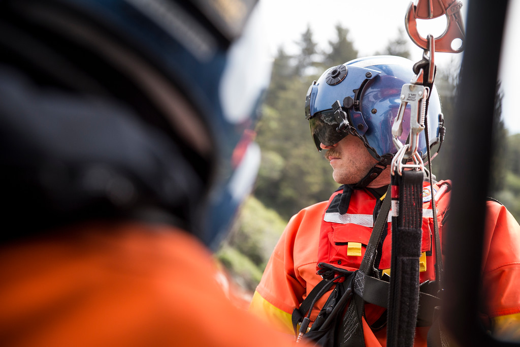 . Rescue swimmer Adam Carr hangs out of the helicopter as the pilots position the helicopter just right in order for Carr to be lowered straight onto the cliff edge of Patrick\'s Point.  (Sam Armanino - Times-Standard)