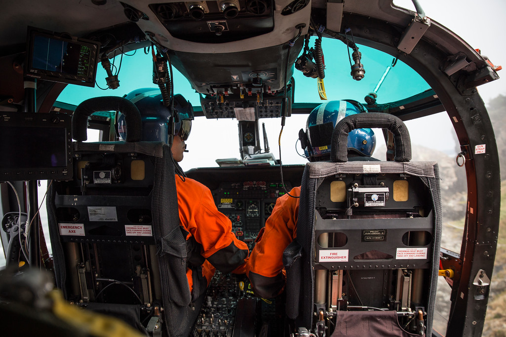 . Lt. Josh Forteza (left) and Aircraft Commander Lt. Matt Fetzner (right) check the weather constantly as North Coast fog begins to roll in while their rescue swimmer is down below.  (Sam Armanino - Times-Standard)