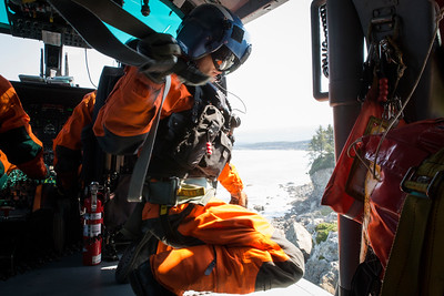 "After Brent Alexander lowered his rescue swimmer Adam Carr out of the helicopter he grabs Carr's ""gunners belt"" to get out of the way so he can lean out of the helicopter.  (Sam Armanino - Times-Standard)"