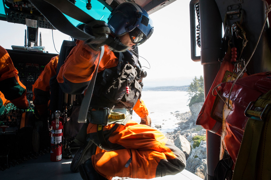 """. After Brent Alexander lowered his rescue swimmer Adam Carr out of the helicopter he grabs Carr\'s \""""gunners belt\"""" to get out of the way so he can lean out of the helicopter.  (Sam Armanino - Times-Standard)"""