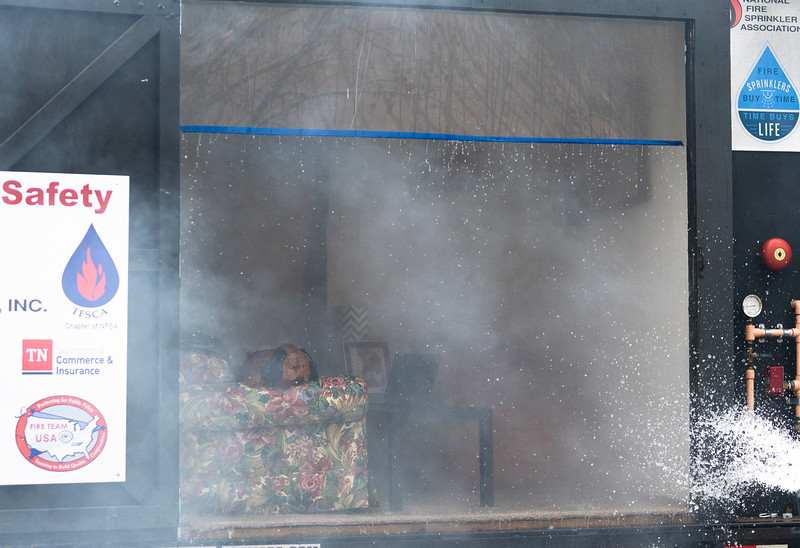 Fire drips from a plexiglass plate after the second of two burns in a side-by-side trailer. This bedroom had fire sprinklers installed and prevented the fire from growing and causing lethal harm.