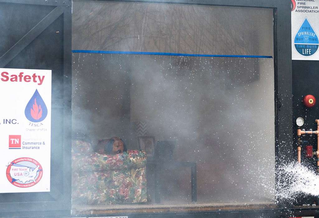 . Fire drips from a plexiglass plate after the second of two burns in a side-by-side trailer. This bedroom had fire sprinklers installed and prevented the fire from growing and causing lethal harm.