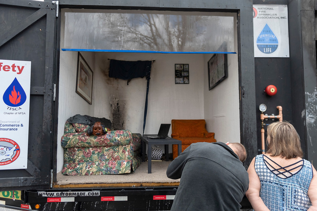 . Residents peer into the second of two bedrooms that were burned during a live demonstration by the National Fire Sprinkler Association on April 24. This bedroom had fire sprinklers equipped so the damage was conderably less than its neighboring room.