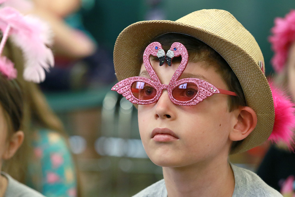 . Benjamin Dill, 11, listens to Leominster Mayor Dean Mazzarella read the book Sylvie by Jennifer Sattler to the children during the celebration of National Pink Flamingo Day at the Public Library on Friday afternoon. SENTINEL & ENTERPRISE/JOHN LOVE