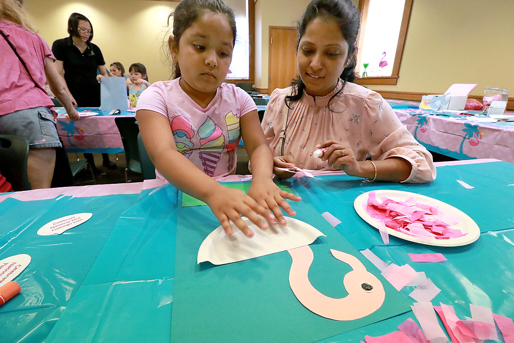 . Himakshi Mishra, 7, and her mom Shifali Mishra work on a flamingo craft during the celebration of National Pink Flamingo Day at the Public Library on Friday afternoon. SENTINEL & ENTERPRISE/JOHN LOVE