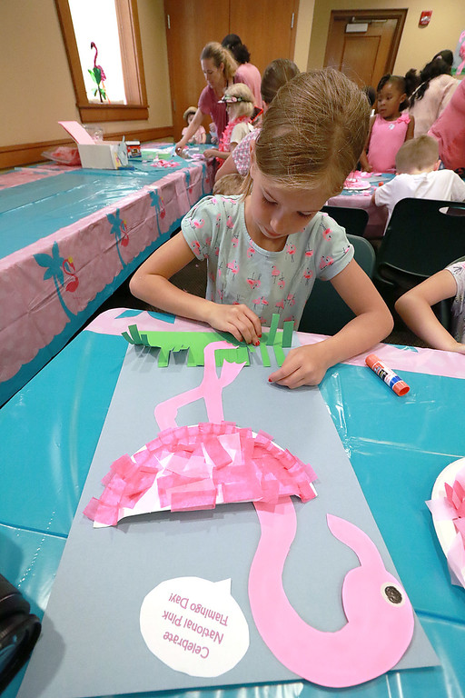 . Emily Zumwalt, 7, from Leominster works on a flamingo craft during the celebration of National Pink Flamingo Day at the Public Library on Friday afternoon. SENTINEL & ENTERPRISE/JOHN LOVE