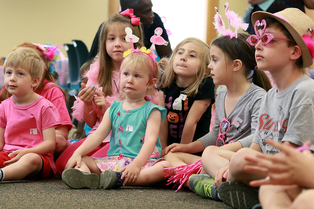 . Kids listens to Leominster Mayor Dean Mazzarella read the book Sylvie by Jennifer Sattler to the children during the celebration of National Pink Flamingo Day at the Public Library on Friday afternoon. SENTINEL & ENTERPRISE/JOHN LOVE
