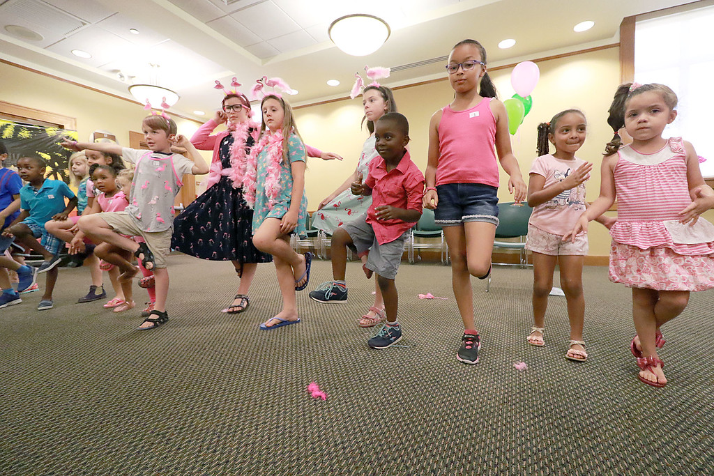 . Kids stand like flamingos during the celebration of National Pink Flamingo Day at the Public Library on Friday afternoon. SENTINEL & ENTERPRISE/JOHN LOVE