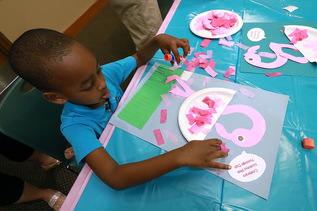 . Garvin Turayishimye, 4, from Leominster works on a flamingo craft during the celebration of National Pink Flamingo Day at the Public Library on Friday afternoon. SENTINEL & ENTERPRISE/JOHN LOVE