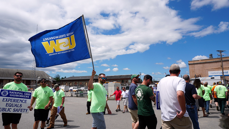 . John Savage of Middleton, who has worked for National Grid for 2.5 years holds a United Steel Workers USW12012-04 Unioun flag as workers block the gate on Rock Street.  (The Sun / Chris Tierney)