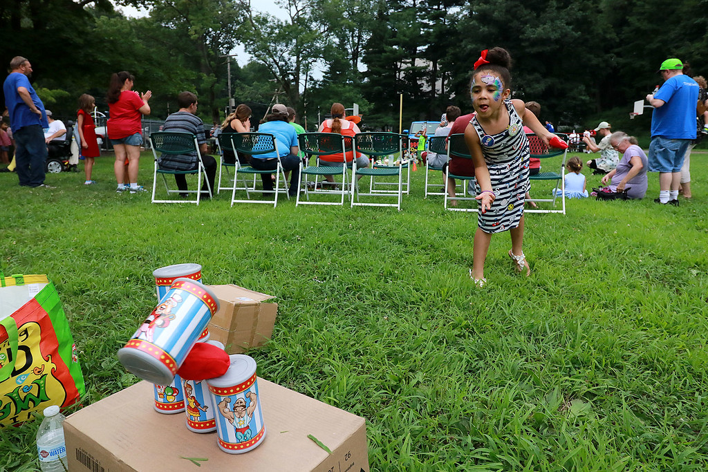 ". ""National Night Out\"" was held at Lowe Playground in Fitchburg on Tuesday night. Delanie Gonzalez, 6, of Leominster shows she has great aim as she knocks over some cans to win a prize at the event. SENTINEL& ENTERPRISE/JOHN LOVE"