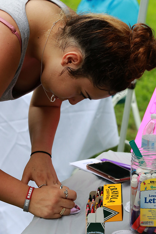 ". ""National Night Out\"" was held at Lowe Playground in Fitchburg on Tuesday night. Coloring a round piece of paper to make a button at the Fitchburg Public Library\'s booth at the event is Yari Rivera, 16, from Fitchburg. SENTINEL& ENTERPRISE/JOHN LOVE"