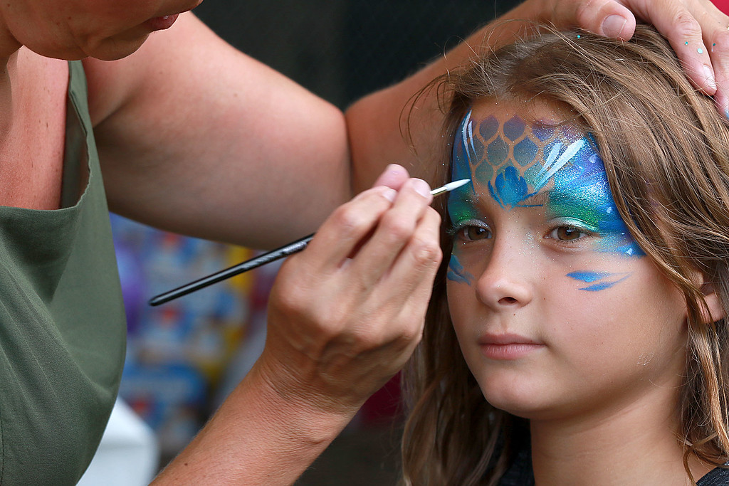 ". ""National Night Out\"" was held at Lowe Playground in Fitchburg on Tuesday night. Adeline VanHazinga, 10, of Fitchburg gets her face painted like a mermaid by Nicole Kirrane at the event. SENTINEL& ENTERPRISE/JOHN LOVE"