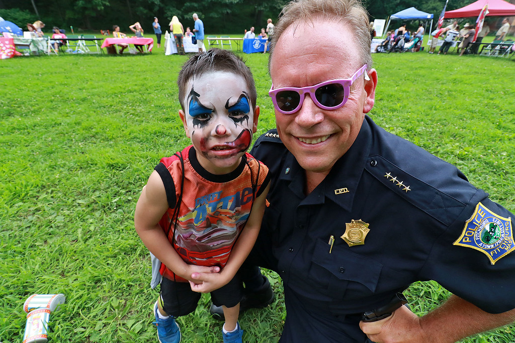 ". ""National Night Out\"" was held at Lowe Playground in Fitchburg on Tuesday night. Marcos Ramos, 5, of Fitchburg poses with Fitchburg Police Chief Ernest Martineau after the chief  knocks down some cans while playing one of the games at the event. Martineau gave his prize pick to Ramos and he picked some purple shades that he asked Martineau to wear for the picture. SENTINEL& ENTERPRISE/JOHN LOVE"