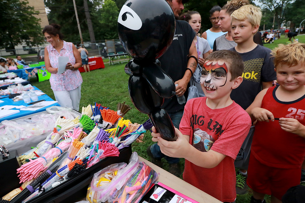 ". ""National Night Out\"" was held at Lowe Playground in Fitchburg on Tuesday night. Many wait in line to get a balloon creature from Ciel Riveras with Balloons by Ciel at the event. Holing a balloon ninja that Ciel just made is Nathan Lemere, 7, of Fitchburg. SENTINEL& ENTERPRISE/JOHN LOVE"