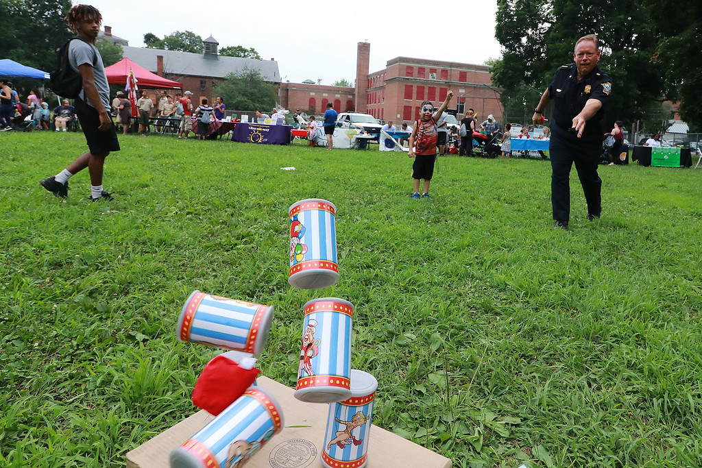 ". ""National Night Out\"" was held at Lowe Playground in Fitchburg on Tuesday night. Marcos Ramos, 5, of Fitchburg cheers on Fitchburg Police Chief Ernest Martineau as he knocks down some cans while playing one of the games at the event. SENTINEL& ENTERPRISE/JOHN LOVE"