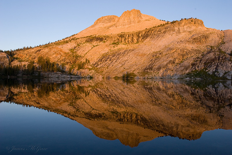 Mt. Hoffman reflected in May Lake glows salmon pink in the first rays of sunrise.  Copyright © 2008 James McGrew.