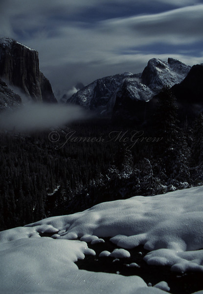 """Midnight Clearing Snowstorm.""  ©2001 James McGrew.  Snow fell on Yosemite Valley for several straight days in March, 2001.  On the night of a full moon, I watched the satellite image on line from home in Mariposa.  I realized that the storm would break sometime in the middle of the night so I drove up to Yosemite Valley, arriving a little after midnight.  By 1:30 am, the storm cleared and moonlight shone down on fresh fallen snow and clouds swirling over the valley walls.  The temperature was in the mid teens but it was so beautiful and I was having so much fun making photographs in the fluffy powder that I scarcely noticed the cold."