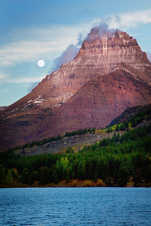 The moon setting behind Swiftcurrent Mountain over Swiftcurrent Lake in Glacier National Park, Montana