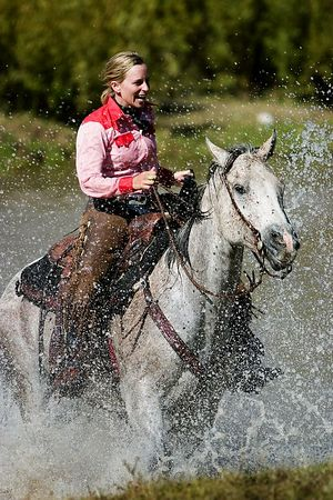 Cowgirl riding through the water in Montana