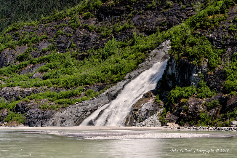 "Nuget Falls (Juneau, Alaska) also known as Nugget Creek Falls or Mendenhall Glacier Falls, is a waterfall downstream of the Nugget Glacier, in the U.S. state of Alaska. Formed by the creek from the Nugget Glacier, the waterfall drops 377 feet (115 m) in two tiers of 99 feet (30 m) and 278 feet (85 m) onto a sandbar in Mendenhall Lake, which is the freshwater pool at the face of the Mendenhall glacier. The lake then drains via Mendenhall River into the Inside Passage.[1] The waterfall is fed by Nugget Creek, which is in turn fed by the Nugget Glacier, a tributary glacier on the mountainside east of Auke Bay. The creek cascades down towards Mendenhall Lake, forming a hanging valley, then plunges over the falls to the lake. Prior to the recession of Mendenhall Glacier, it was said that the falls would drop ""directly on the glacier"" or that the ""glacier covered the waterfall""."