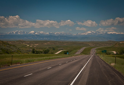 The road to Cody WY and Yellowstone with snow capped Rocky Mountains in the background.