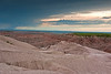 Eroded buttes with its pinnacles and spires. To the left you can see a storm moving in over the Badlands.