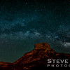 A panorama of the mountains that ring the Chisos Basin with the Milky Way arcing above Casa Grande.