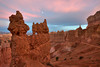 The moon shines above a hoodoo during sunset in Bryce Canyon National Park. The Sentinel is visible above a hiker on the Navajo Loop trail.