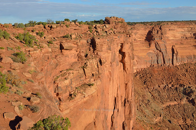 Lisa walking the rim trail at Dead Horse Point Overlook. She is visible as the aqua dot about a third of the way in at the top of cliff from the left side.