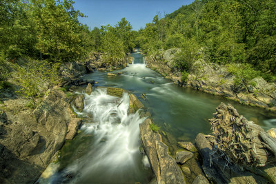 Water tumbles over rock edges beneath a bridge at the Chesapeake & Ohio Canal National Historical Park in Potomac, MD on Sunday, August 16, 2015. Copyright 2015 Jason Barnette