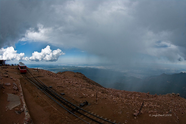 Cog Railway car at the summit.  Note the blue clear sky on the left and the snow on the right.