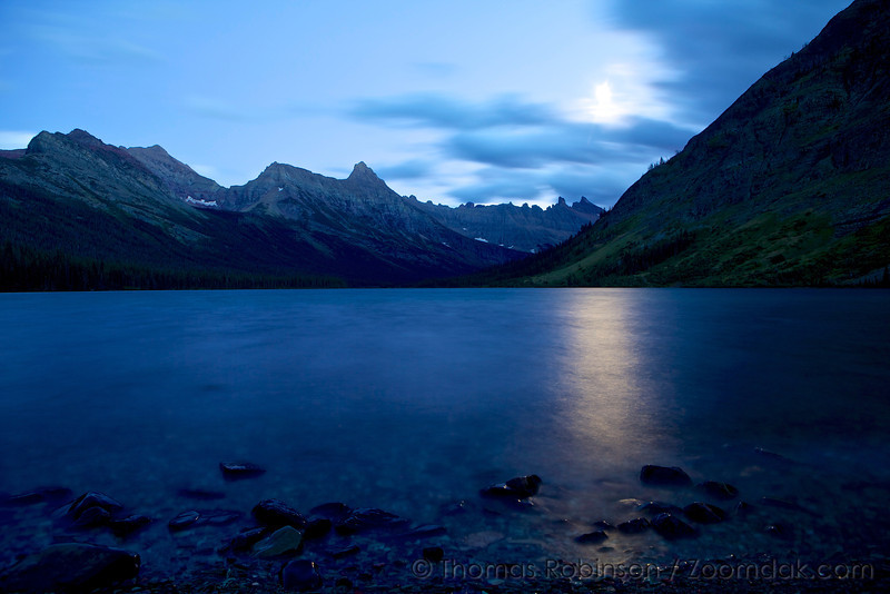 The moon light refracts upon Elizabeth Lake on a cloudy evening. The Ptarmigan Wall and Iceberg peak stand strong in the distance as seen from Elizabeth Lake Foot Campsite.