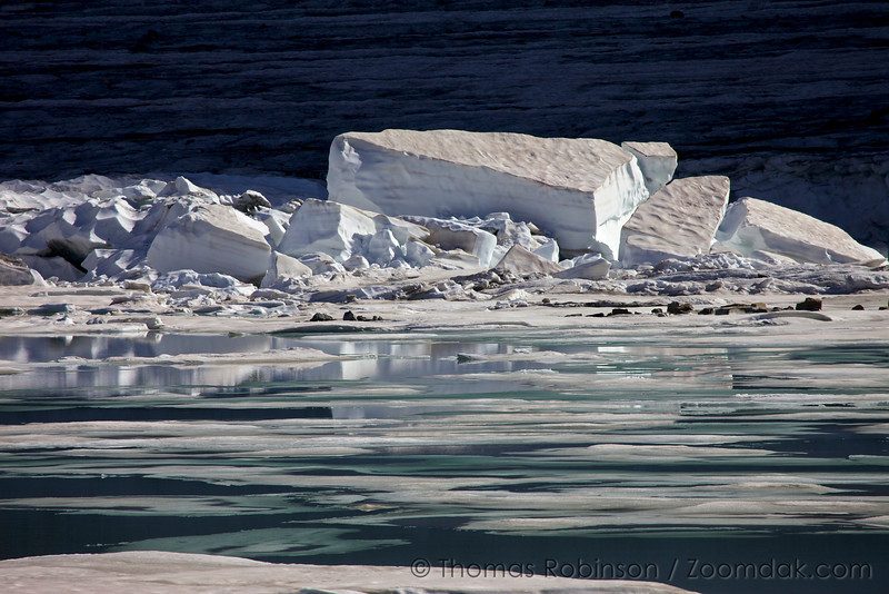 Icebergs the size of a house break of Grinnell Glacier to float on Upper Grinnell Lake in Glacier National Park.